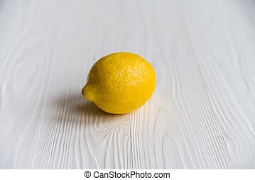 Close up fresh ripe lemon covered in water drops on white wooden surface