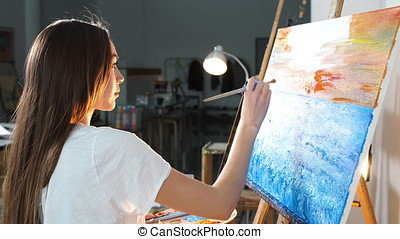 Single woman artist producing picture on canvas with oil...