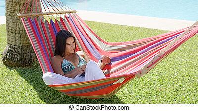 Single woman in bikini reading a book in hammock