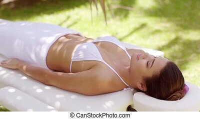 Single woman laying down in outdoor beauty spa
