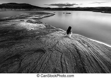 Single Woman sitting by the lake black and white
