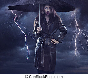 Single woman wearing coat holding umbrella. Creative szmbol of the bad weather