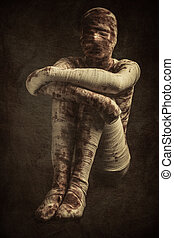 Single young bloody mummy sits in the darkness with arms...