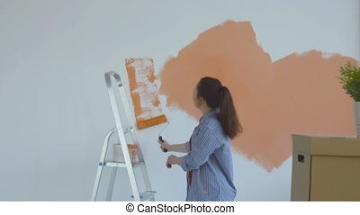 Young woman paints her walls orange with a roller