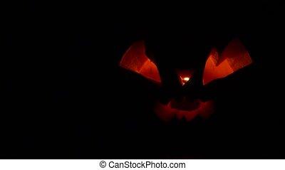 Sinister Halloween pumpkin flickers red infernal light in ...