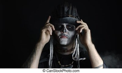 Sinister man with Halloween skeleton makeup. Female hand ...