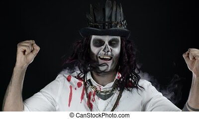 Sinister man with horrible Halloween skeleton makeup in shirt with blood celebrating, dancing, showing thumbs up. Horror theme. Day of The Dead. Isolated on black background. 6k downscale, slow motion