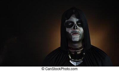 Sinister man with horrible Halloween skeleton makeup in costume with hood making faces, looking at camera, trying to scare. Horror theme. Day of The Dead. Isolated on black background. 6k downscale