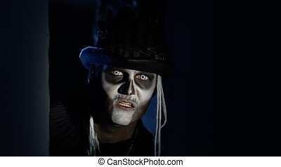 Sinister man with horrible Halloween skeleton makeup in costume with top-hat quickly appears from dark corner trying to scare. Horror theme. Shooting in dark parking hallway. 6k downscale, slow motion