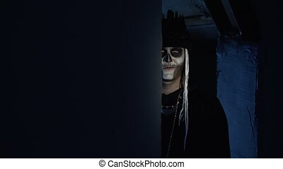 Sinister man with horrible Halloween skeleton makeup in costume with top-hat slowly appears from dark corner with wide, frightening smile. Horror theme. Shooting in dark parking hallway. 6k downscale