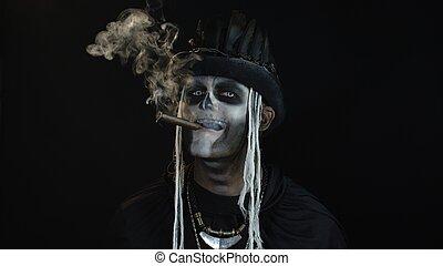 Sinister man with horrible Halloween holiday skeleton makeup raising his head and smoking cigar