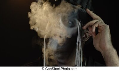 Close-up shot of sinister man with Halloween holiday skeleton makeup in costume raising his head and smoking cigar, making faces, looking at camera. Horror theme. Day of The Dead. 6k downscale