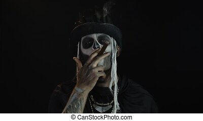 Sinister man with horrible Halloween holiday skeleton makeup in costume with top-hat raising his head and smoking cigar, making faces, looking at camera. Horror theme. Day of The Dead. 6k downscale