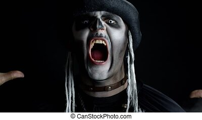 Sinister man with horrible Halloween skeleton makeup appearing from darkness when light falls on him, making faces, trying to scare. Horror theme. Dark black background. 6k downscale, slow motion