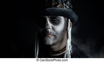 Sinister man with horrible Halloween skeleton makeup appearing from darkness when light falls on him, making faces, looking at camera. Horror theme. Black background. 6k downscale, slow motion