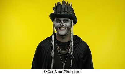 Sinister man with horrible Halloween skeleton makeup in costume with top-hat making faces, looking at camera, showing tongue. Horror theme. Day of The Dead. Yellow background. 6k downscale. Copy space