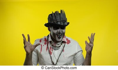 Sinister man with horrible Halloween skeleton makeup in costume with top-hat making faces, looking at camera trying to scare. Horror theme. Day of The Dead. Yellow background. 6k downscale. Copy space