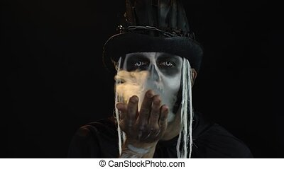 Sinister man with horrible Halloween skeleton makeup in costume with top-hat showing hands and making fly air kiss with smoke. Horror theme. Day of The Dead. Isolated on black background. 6k downscale