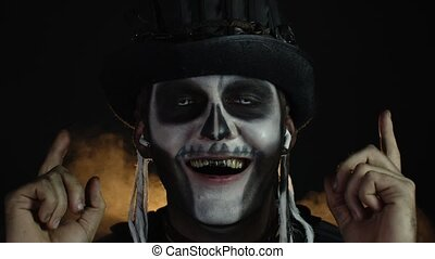 Sinister man with horrible Halloween skeleton makeup with top-hat puts on headphones and starts dancing, celebrating. Horror theme. Day of The Dead. Isolated on dark black background. 6k downscale