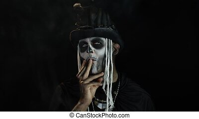 Sinister man with horrible Halloween skeleton makeup in costume with top-hat smoking cigar, making faces, looking at camera. Horror theme. Day of The Dead. Isolated on black background. 6k downscale