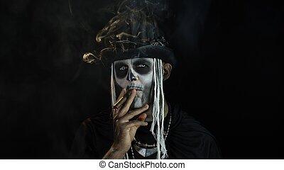 Sinister man with horrible Halloween skeleton makeup smoking cigar, making faces