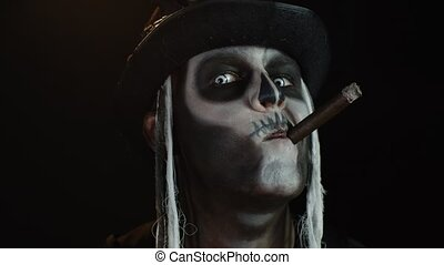 Sinister man with horrible Halloween skeleton makeup in costume with top-hat smoking cigar, making faces, smiling, laughing. Horror theme. Day of The Dead. Isolated on black background. 6k downscale
