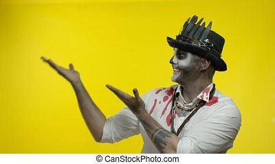 Sinister man with horrible Halloween skeleton makeup in bloody shirt looking at camera trying to scare, pointing to the left. Copy space. Horror theme. Day of The Dead. Yellow background. 6k downscale