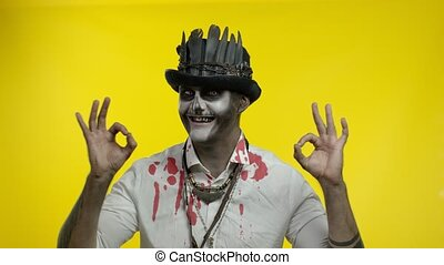 Sinister man with horrible Halloween skeleton makeup in white bloody shirt making faces, looking at camera, showing ok sign. Horror theme. Day of The Dead. Isolated on yellow background. 6k downscale