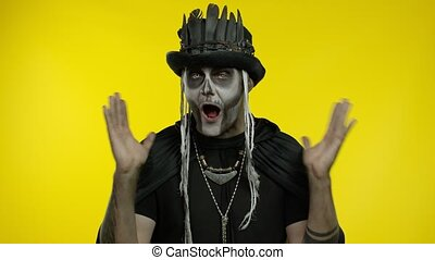 Sinister surprised man with horrible skeleton makeup in costume with top-hat saying wow in amazement, received shocking good news. Halloween thematic party. Isolated on yellow background. 6k downscale