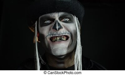 Sinister man with skull makeup appearing on black background...