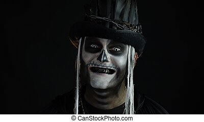 Sinister man with skull makeup opening his mouth and showing dirty black teeth. Halloween skeleton