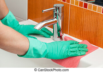 Sink cleaning - A man cleaning a sink with a rag