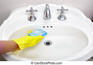 Sink cleaning. - Hand of housewife with blue sponge cleaning...