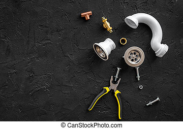 Sink drain parts and plumbing tools on black background top view copyspace