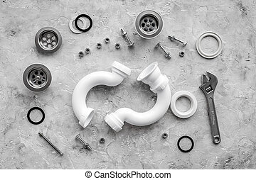 Sink drain parts and plumbing tools on grey stone background top view