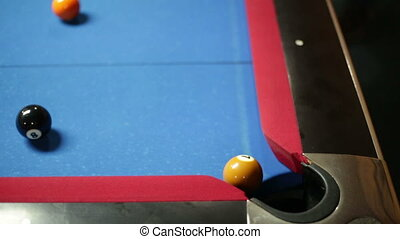 Game of pool with blue felt pool table sinking ball 7 in corner pocket