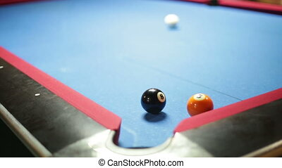 Game of pool with blue felt pool table, sinking black ball in corner pocket
