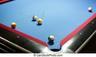 Game of pool with blue felt pool table, sinking green ball in corner pocket