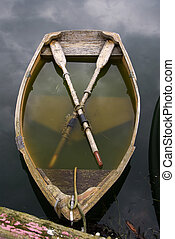 Sinking Rowboat - Rowboat partially underwater while still...