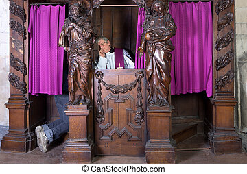 Feet of a person in a confession booth and the priest listening (shot in a medieval 17th century church)