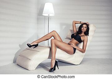 sinnlich, brünett, frau, mit, langer, lockenkopf, liegen, in, weißes, bett, posierend, in, sexy, schwarz, damenunterwäsche, anschauen, kamera.