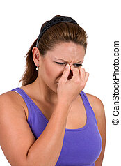 Woman holds the bridge of her nose suffering from sinus congestion.