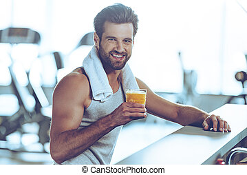 Sip of freshness after great workout. Side view of handsome young men in sportswear holding glass of fresh orange juice and looking at camera with smile while sitting at bar counter at gym