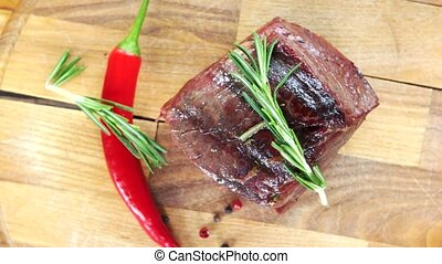 Sirloin steak top view. Beef, rosemary and chili pepper.
