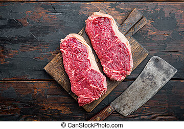 Sirloin steak, uncooked beef meat, on dark wooden background, top view, with copy space for text