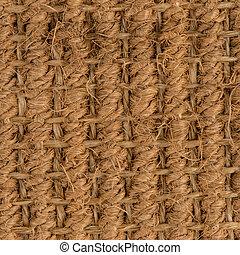 Closeup detail of a brown sisal carpet texture background.
