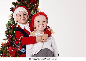 Sister and brother hugging under Christmas tree