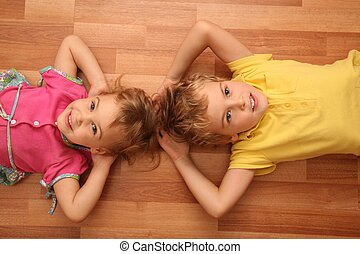 sister and brother lie on floor