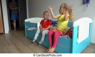 Sister and brother sit on bed clap hands and loving father man. Gimbal motion