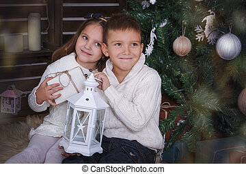 Sister and brother sitting under Christmas tree with gifts